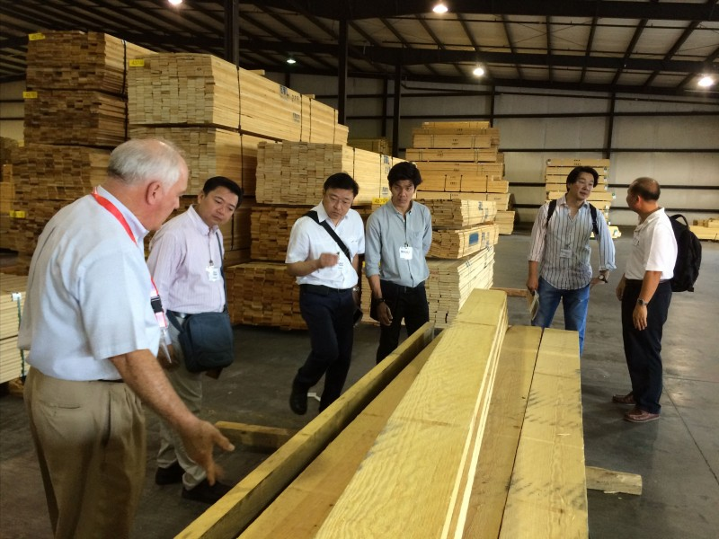 A delegation of Thai lumber company executives (including Opas Panitchewakul, Pracha Thawornjira, Jaroonsak Cheewatammanon, Khomwit Boonthamrongkit and Wasant Sonchaiwanich) tours the Mauvila Timber distribution warehouse in Loxly, Ala., with Lane Merchan
