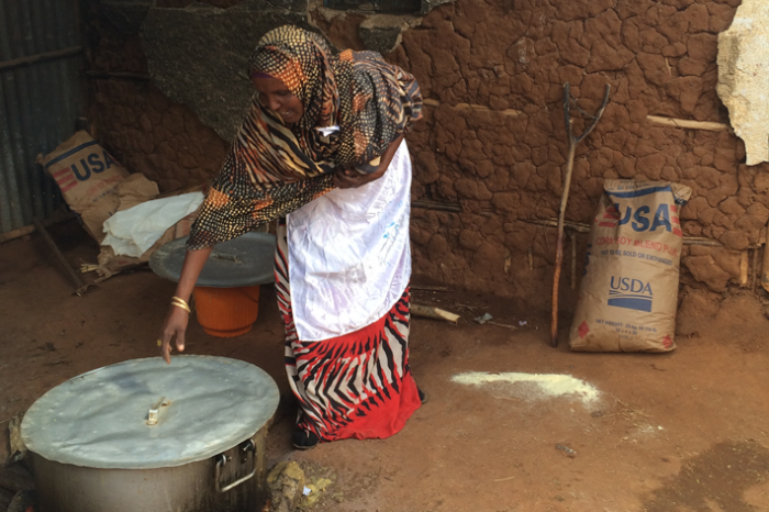 A parent volunteer uses USDA-supplied corn-soy blend to prepare a nutritious porridge for school children in eastern Ethiopia.