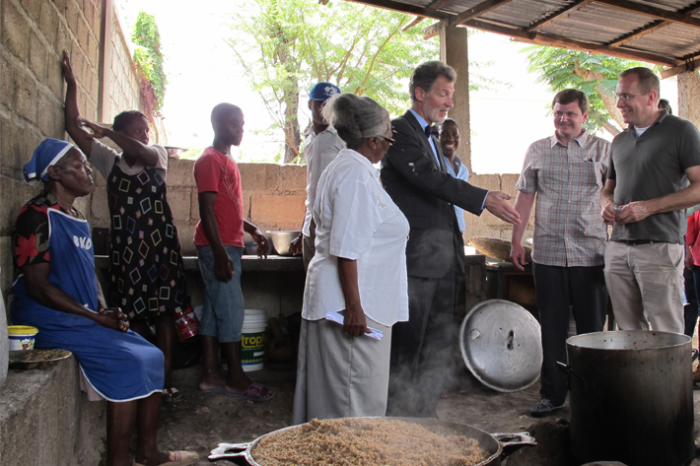 Marie Juslene Pelerin (in white), principal of Haiti's National School of Ganthier, shows the preparation of a school meal to U.S. Ambassador to Haiti Peter Mulrean (to her right) and FAS Administrator Phil Karsting (far right).