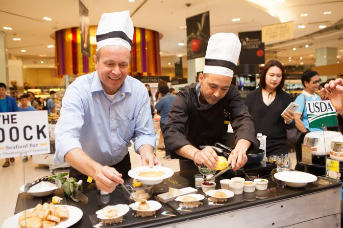FAS Administrator Phil Karsting serves as sous chef to Chef Benjamin B. from the DOCK Seafood Bar to prepare U.S. Scallop Tom Yam Au Gratin. The DOCK Seafood Bar is operated by Thailand's largest importer of U.S. seafood, Thammachart Seafood Retail. Photo