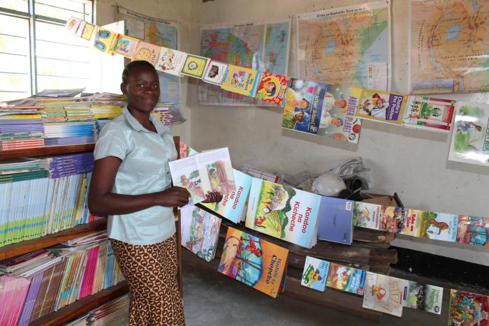 A teacher in the Mara region of Tanzania proudly shows her classroom full of learning resources in a reading-corner she created with help from PCI's McGovern-Dole program. The program is more than a school feeding program, it also helps feed students' app