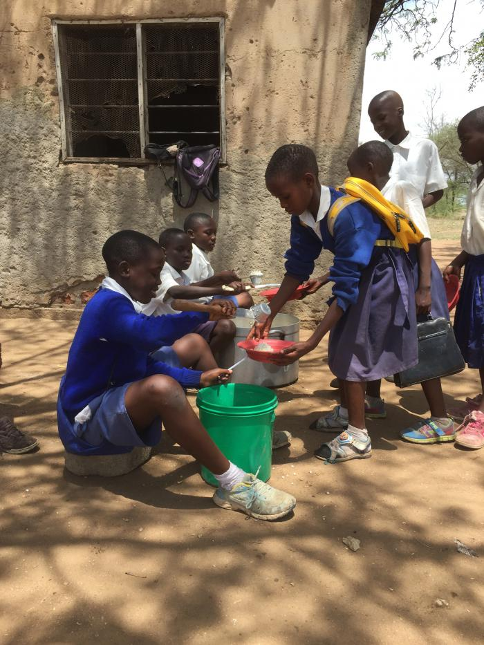 Violet receives a nutritious meal of USDA-provided rice, fortified vegetable oil and beans, complemented with bright green amaranth leaves donated by school parents. PCI is collaborating with the local government to ensure students continue to benefit fro