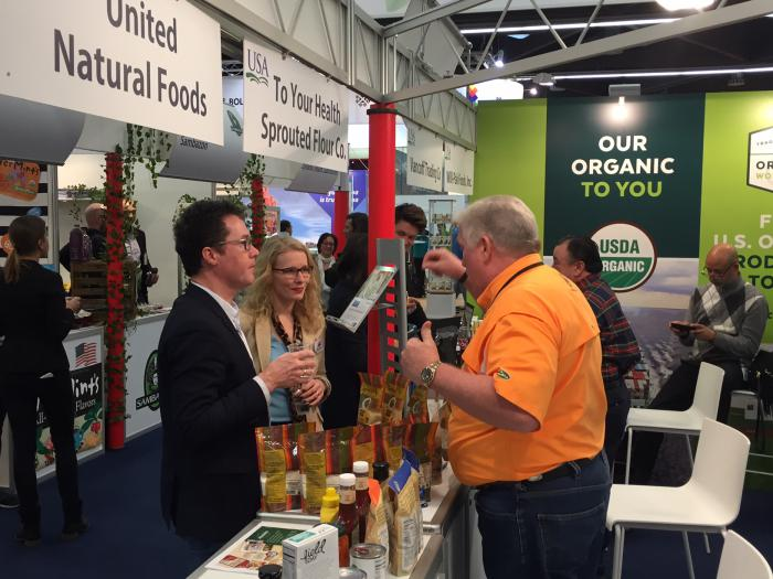 Harald Ebner, Member of German Parliament, tours the USA Pavilion with Kelly Stange, Agricultural Counselor at the U.S. Embassy in Berlin, and meets Jeff Sutton, CEO of To Your Health Sprouted Flour Co.  from Alabama.