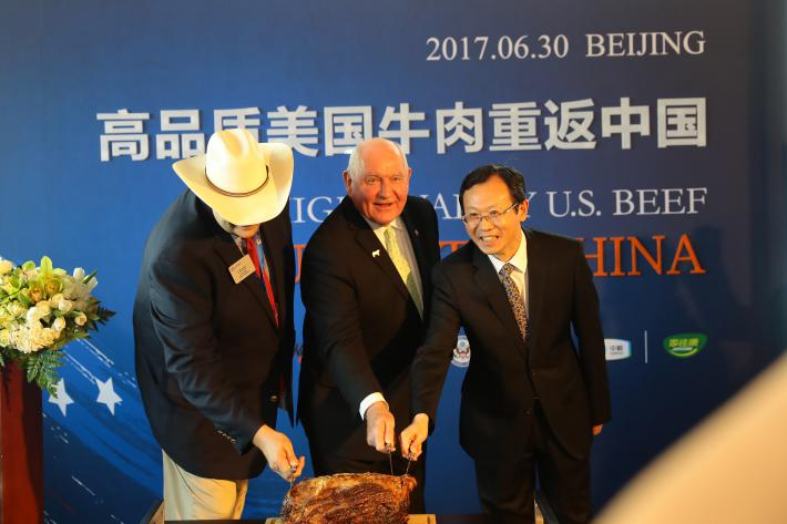 U.S. Secretary of Agriculture Sonny Perdue (center) ceremonially cuts into a Nebraska prime rib in Beijing, marking the return of U.S. beef to the Chinese market. Perdue is joined by Craig Uden (left), president of the National Cattlemen's Beef Associatio