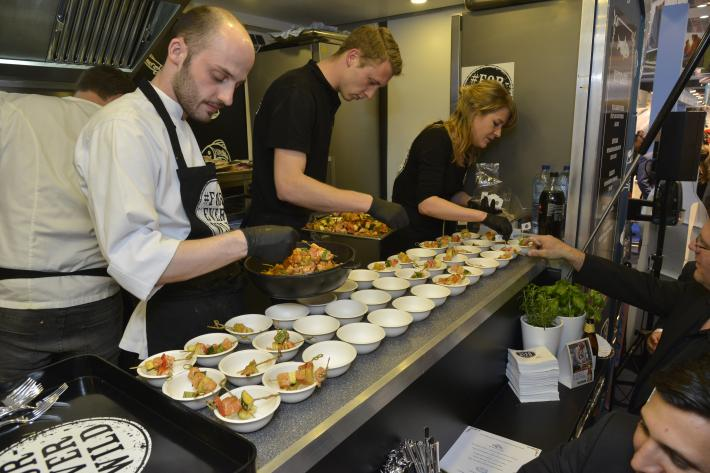 A food truck in the USA Pavilion at Seafood Expo Global attracts a crowd as the chef dishes up fresh, high-end seafood bites and snacks made with Alaskan salmon, cod and scallops.
